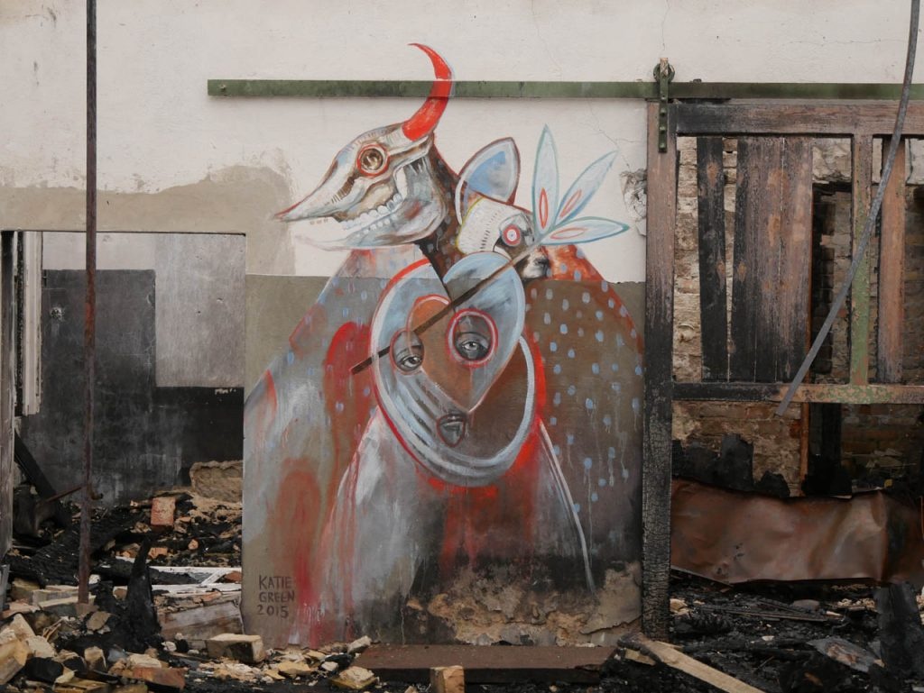 A beautiful picture surrounded by burned wood. How long will it last? What's the painters intention, when sooner or later his art is destroyed? Graffiti never lasts long and that's what it makes special to me.